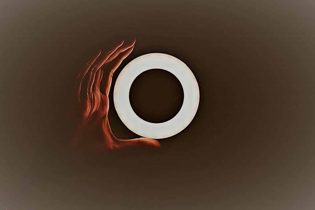 Eine Hand hält ein leuchtendes Objekt in der Hand, das Objekt sieht aus wie der Buchstabe O. Der Buchstabe O wird hier im Zusammenhang mit der Website Osteopathie Reichel gesehen,